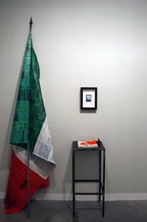 """Quaderno di Sogni<br>GMT01<br>bandiera carta di giornale, asta di ferro H 270 cm<br>foto 22x 30 cm<br>tavolino 90 h x 40 x 40 cm<br>tecnica: installazione<br>anno: 2017<br><br><span style=""""color:red"""">NON DISPONIBILE</span>"""